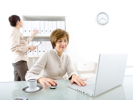 Two businesswomen and assistant working in the office. photo