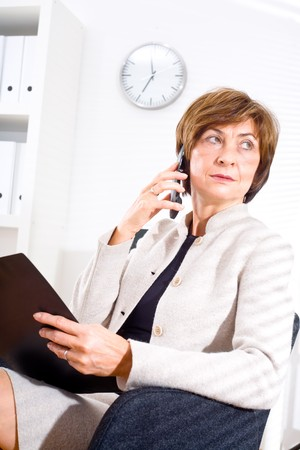 Senior businesswoman looking through window while calling on phone and working at office. photo