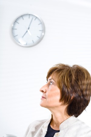 Mature businesswoman sitting at office and looking up to office clock. photo