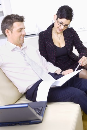 Happy businesspeople teamworking on sofa at office, smiling. Stock Photo - 4153331