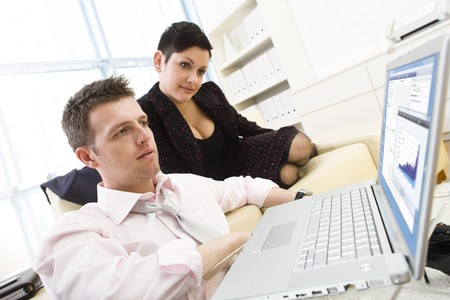 teamworking: Businessman sitting on floor and teamworking on laptop computer with businesswoman. They look workoholic.  Stock Photo