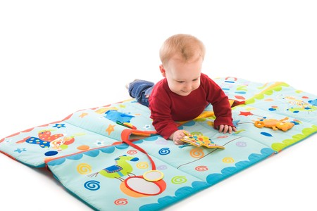 Happy baby boy (6 months old) playing with soft toys, smiling. Toys are property released. Stock Photo