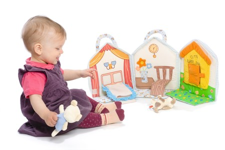 Baby girls sitting on floor playing with stuffed story book. Isolated on white. Toys are officially property released. Stock Photo - 4153312