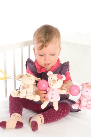 Cute baby girl (1 year old) sitting on crib, holding soft toys. Isolated on white, smiling. Toys are offically property released. Stock Photo - 4153323