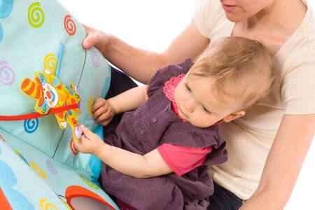 Mother reading for baby girl (9 months) from story book. photo