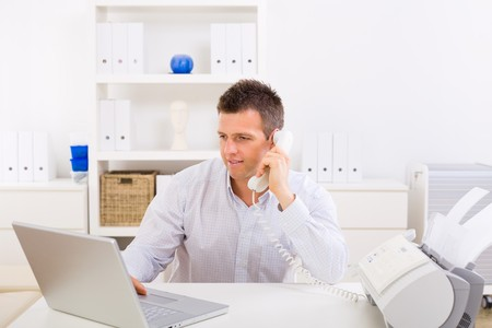 Business man working on computer at home calling on phone. Stock Photo - 4153317