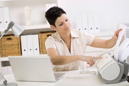 outwork: Mujer mediante fax en la oficina de casa.