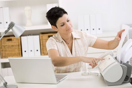 teleworking: Woman using fax machine at home office. Stock Photo