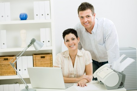 sinecure: Happy couple working at home using laptop computer, smiling.