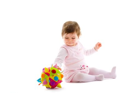 Happy baby girl sitting on floor playing with toy smiling, isolated on white background. photo