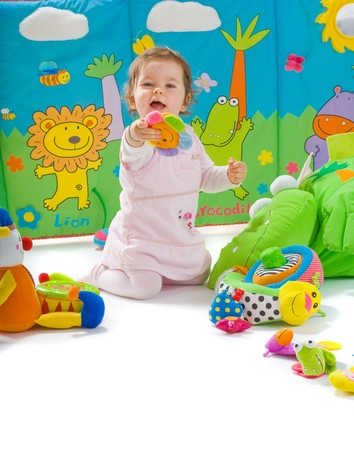 kid friendly: Happy baby playing with soft toys, smiling, isolated on white background.