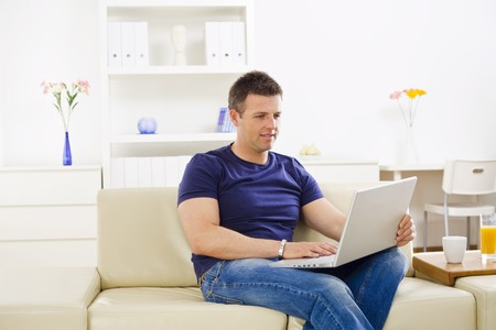 outworking: Man browsing internet on laptop computer at home.