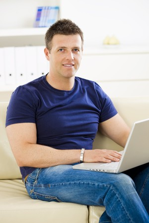 Man sitting on sofa at home and using laptop computer. Stock Photo - 4153335
