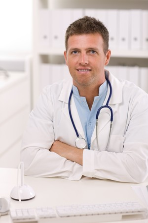 Happy male doctor working at office, smiling. photo