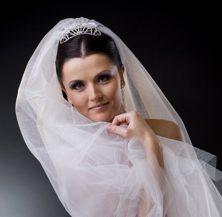 Portrait of a smiling young bride wearing a white wedding dress, holding her veil lloking at camera. photo