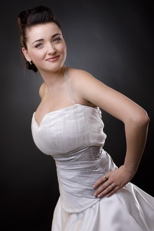 Happy bride standing with arm on hips in a white wedding dress, smiling and looking at camera. photo