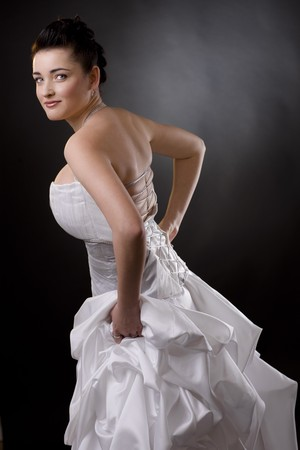 Portrait of a bride posing in a white wedding dress, holding her skirt and looking at camera. Stock Photo - 4153324