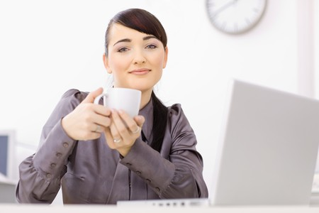 Businesswoman sitting at her desk in the office drinking coffe, smiling. photo