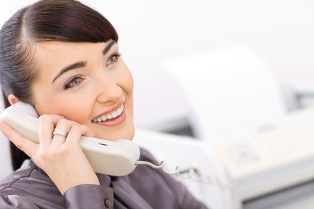Happy businesswoman talking on landline phone in a bright office. photo