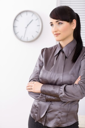 Casual youg businesswomen standing arms crossed in office, smiling. photo
