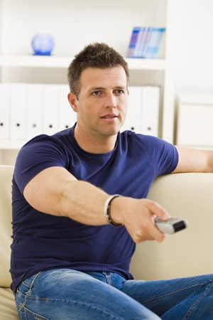 Man sitting on sofa watching TV at home. photo