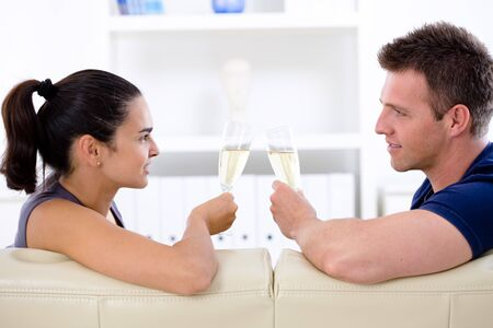 Love couple drinking champagne at home on sofa. Stock Photo - 4161085