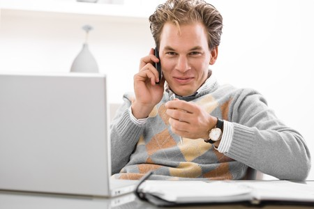 Young man using laptop and calling on phone at home. Stock Photo - 4161123