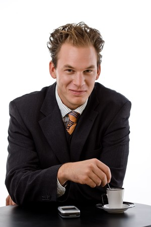Businessman drinking at coffee table, smiling, white background. photo