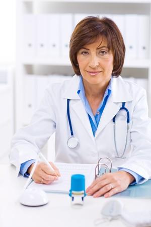 Senior female doctor sitting at desk working at offiice. photo