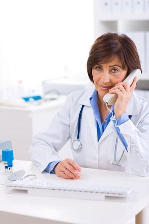 Senior female doctor calling on phone, smiling. photo