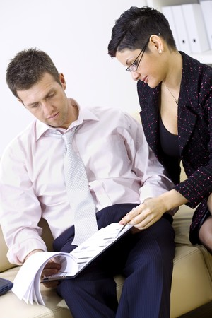 Businesspeople working together, stitting on couch looking at business report. photo