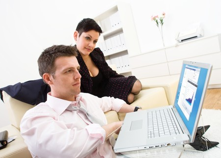 Businessman and businesswoman working together at office, sitting on sofa and using laptop computer. Close-up Stock Photo - 4161158