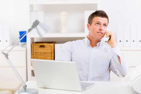 sinecure: Business man working on computer at home calling on phone.