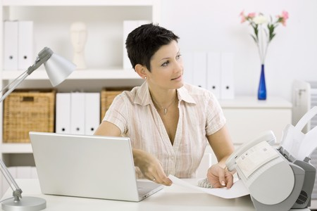 telework: Woman using fax machine at home office. Stock Photo