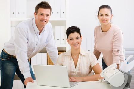 empleadas domesticas: Equipo de oficina felices las personas que trabajan en la computadora port�til, sonriendo.