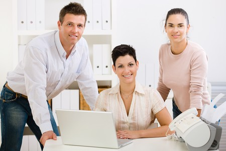 Team of happy office people working on laptop computer, smiling. Stock Photo - 4161231