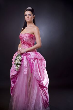 Portrait of a happy young bride posing in a pink wedding dress, holding bouqet of white flowers. photo