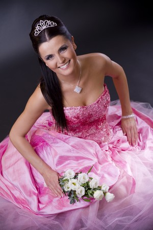 Happy young bride posing in a pink wedding dress, holding bouqet of white flowers.