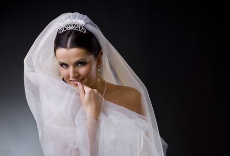 wedding gown: Portrait of a smiling young bride wearing a white wedding dress, holding her veil lloking at camera.