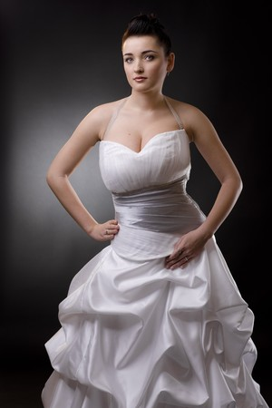bridal dress: Bride posing in a white wedding dress, arms on hips, looking at camera. Stock Photo
