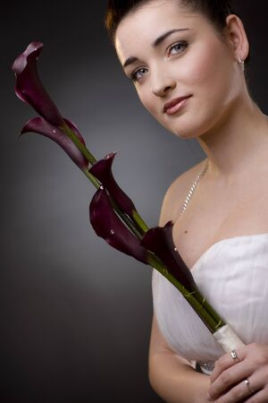 Closeup portrait of a bride posing in a white wedding dress, holding purple flowers looking at camera. photo