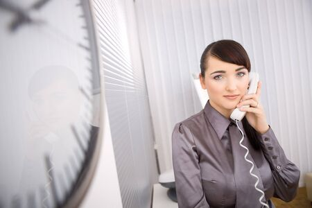 Young businesswoman talking on landline phone in the office, looking at camera. Stock Photo - 4161159