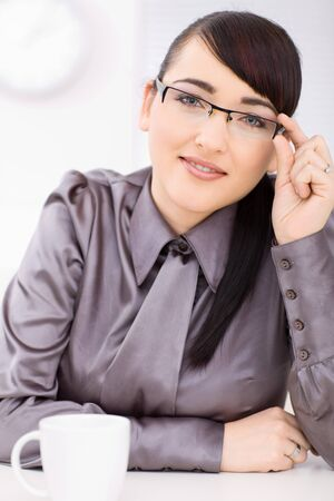 Intelligent young businesswomen looking at camera, smiling, holding her glasses. photo