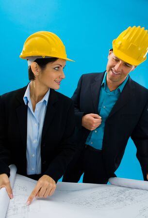 Young architects wearing hardhat looking at blueprint, isolated on blue. photo