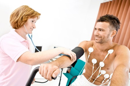 Nurse makes the patient ready for medical EKG test. Real people, real locacion, not a staged photo with models.