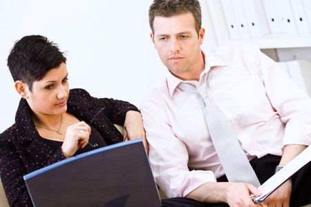 Businessman and businesswoman reviewing documents together on laptop computer at office. photo