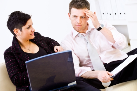 Businessman and businesswoman working together, sitting of sofa, holding laptop and looking troubled. photo