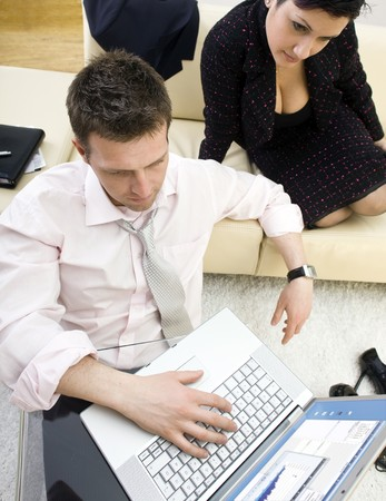 Businessman sitting on floor and teamworking on laptop computer with businesswoman. They look workoholic. High-angle view. photo