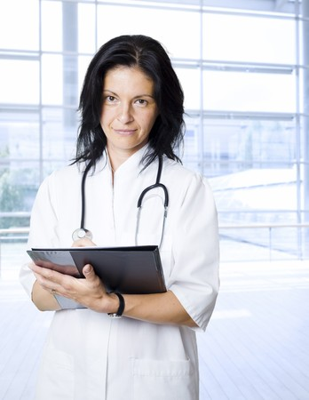 Portrait of happy female doctor in hospital lobby, smiling, holding folder. Stock Photo - 4175666
