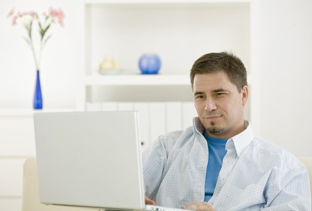 Happy casual man teleworking using laptop computer at home. Stock Photo - 4175678